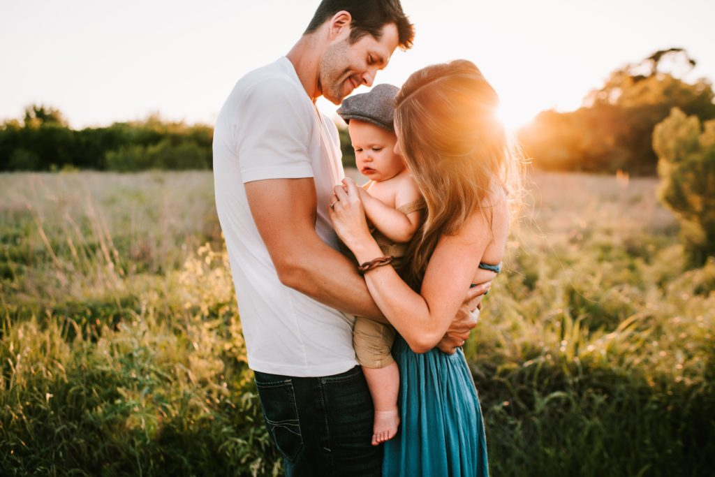 A family Photographer photo- couple holding baby in a field at sunset for photoshoot