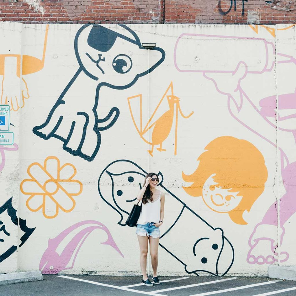 woman with sunglasses in front of mural in parking lot in portland oregon